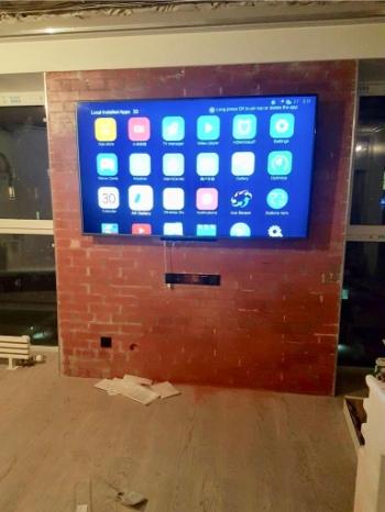 Большой телевизор закреплен к кирпичной стене